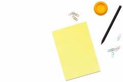 黄色笔记薄、黑铅笔和一个纸夹在白色背景 办公室的最小的概念工作场所 平的位置 图库摄影