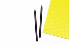 黄色笔记薄和两黑铅笔在白色背景 工作地点的最小的企业概念在办公室 免版税库存照片