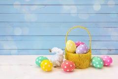 黄色篮子用复活节彩蛋和一只兔子在蓝色背景 库存照片