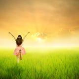 绿色米领域和日落的愉快的妇女 免版税库存图片