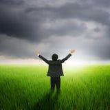 绿色米领域和rainclouds的愉快的商人 图库摄影