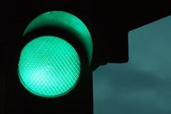 绿色红绿灯在夜之前和在背景的黑暗的天空 免版税图库摄影