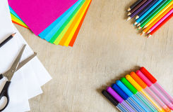 色纸、毡尖的笔、铅笔和剪刀在木背景 库存图片