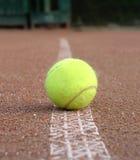 黄色网球在室外法院标号线放置 库存图片