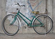 绿色老自行车和墙壁 免版税库存图片