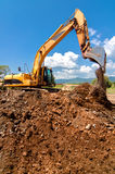 黄色耐用工业挖掘机工作 免版税库存照片