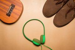 绿色耳机、尤克里里琴和起动在包装纸背景 免版税库存照片