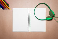 绿色耳机、笔记本、笔和颜色铅笔在一张包装纸 库存照片