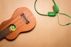 绿色耳机和尤克里里琴在包装纸背景 免版税库存照片