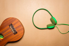 绿色耳机和尤克里里琴在包装纸背景 库存图片