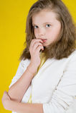 黄色背景的严肃的八岁的女孩 库存照片