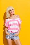 黄色背景的微笑的白肤金发的妇女 免版税库存照片