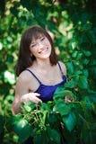 绿色背景的美丽的女孩在夏天公园离开 免版税图库摄影