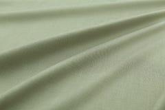 绿色背景豪华布料或难看的东西丝绸纹理缎天鹅绒波浪折叠  库存照片