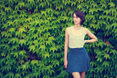 绿色自然背景的逗人喜爱的行家女孩 免版税库存图片