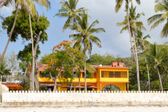 黄色色房子在一个热带庭院里 免版税库存照片