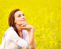 黄色花卉领域的逗人喜爱的女性 免版税图库摄影