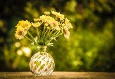 黄色花小花束在一张老木桌上的 复制空间 库存照片