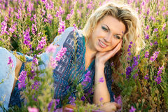 紫色花的微笑的妇女 库存照片