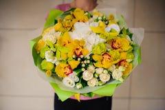 黄色花美丽的花束在手上女孩 免版税库存照片