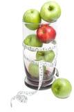 绿色苹果和与测量的磁带的红色苹果在玻璃碗 库存图片