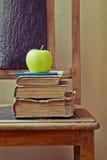绿色苹果和旧书在一把老椅子与葡萄酒感觉 库存照片