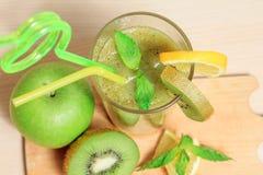 绿色苹果和猕猴桃圆滑的人用柠檬和薄菏 免版税库存照片
