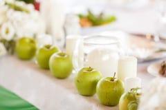绿色苹果和白色蜡烛作为饭桌12月的元素 图库摄影