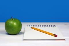 绿色苹果和笔记本有铅笔的在白色木书桌上 免版税库存照片