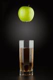 绿色苹果和苹果汁到一块雕琢平面的透明玻璃里 库存照片