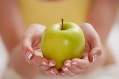 绿色苹果在妇女手上 免版税库存照片