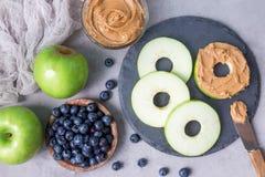 绿色苹果环绕用花生酱,并且在板岩的蓝莓上,水平,顶视图 免版税库存照片