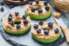 绿色苹果环绕用花生酱,并且在板岩的蓝莓上,水平 库存照片