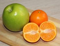 绿色苹果计算机和桔子在桌上 库存图片