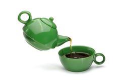 绿色茶壶倾吐的茶到一个绿色杯子里 免版税库存图片