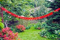 绿色草坪在用心脏装饰的庭院里 免版税库存图片