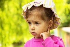 绿色草坪夏天背景的小逗人喜爱的女孩 免版税库存图片