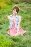 绿色草甸的美丽的亚裔女孩 免版税库存照片