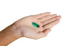 绿色药片在手边 免版税库存图片