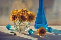 黄色菊花花束在窗口的 蓝色瓶和玻璃球 仍然1寿命 库存图片