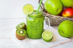 绿色菜和果子圆滑的人,篮子用苹果,猕猴桃,石灰,阳光 免版税库存图片