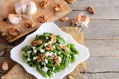 绿色菜豆沙拉食谱 芳香抚人的绿色菜豆沙拉用酸奶干酪、被剥皮的核桃、大蒜和香料 免版税库存图片
