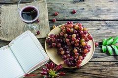 紫色葡萄板材,红葡萄酒玻璃,在老木桌安置的笔访 免版税库存照片