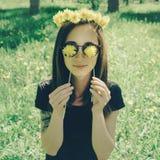 黄色蒲公英花圈的微笑的美丽的女孩  免版税库存图片