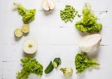 绿色蔬菜和水果的汇集在白色木背景 顶视图 文本的空间 免版税库存照片