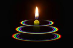 绿色蜡烛光在三个彩虹圆环的 库存照片