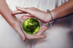 绿色行星地球在女性手上 免版税库存图片
