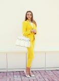 黄色衣服的美丽的少妇穿衣与提包摆在 图库摄影