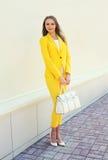 黄色衣服的美丽的少妇穿衣与提包 免版税库存照片