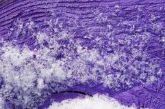 紫色表面上的雪! 库存图片